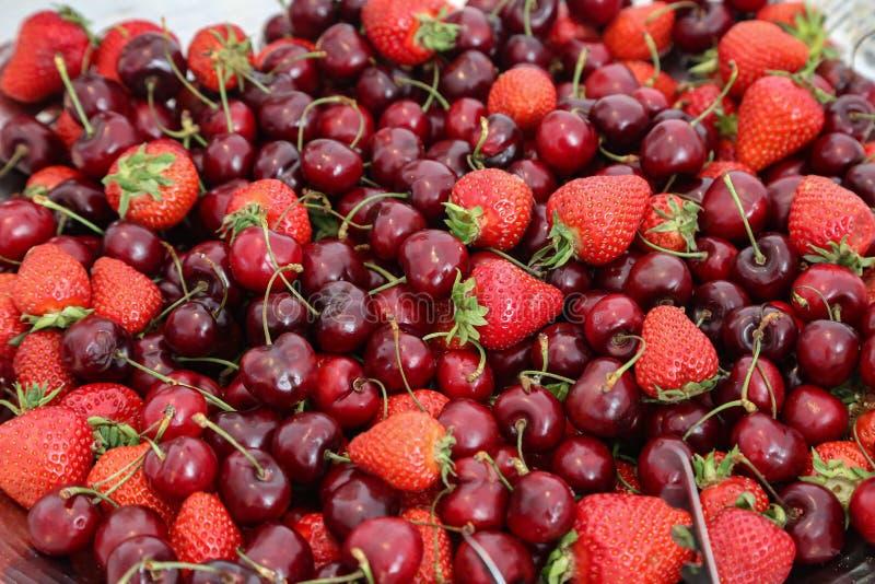 Morangos maduras e cerejas dispersadas na tabela fotos de stock royalty free