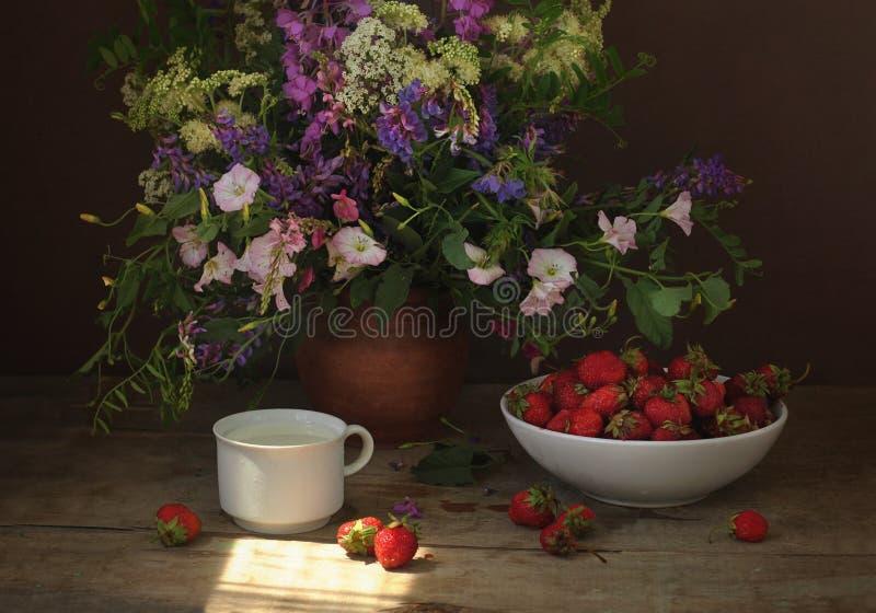 Morangos maduras em uma placa branca, em uma caneca de leite e em um ramalhete dos wildflowers em uma tabela de madeira Ainda vid imagens de stock royalty free