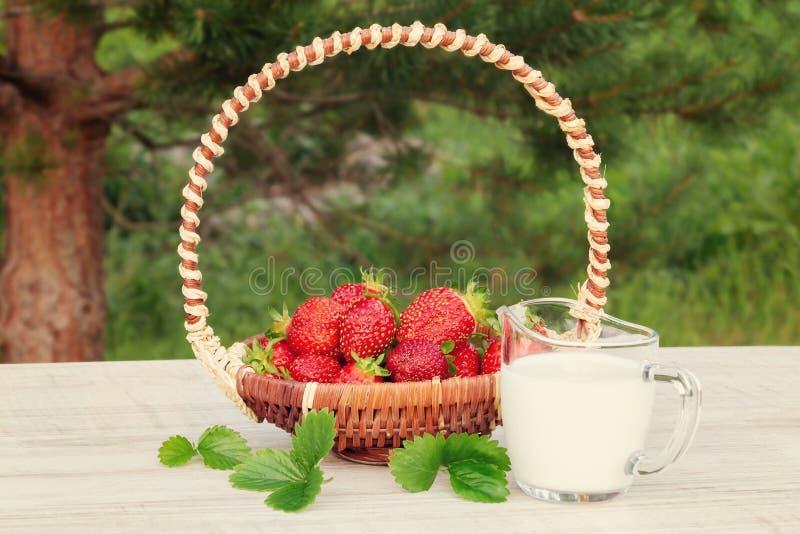 Morangos maduras frescas em uma cesta e em um iogurt em uma tabela de madeira fora em um dia de verão fotos de stock