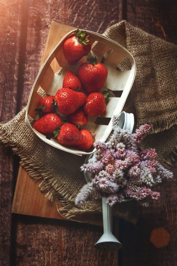 Morangos vermelhas frescas na tabela de madeira com flores do verão, café da manhã, estilo do eco, tiro acima, tonificado fotos de stock