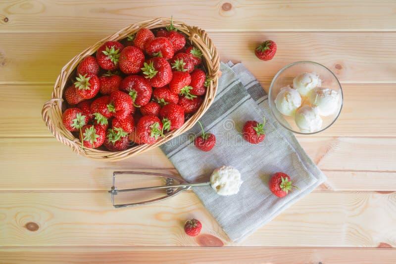 Morangos vermelhas maduras no gelado da cesta e da sundae na tabela de madeira imagens de stock