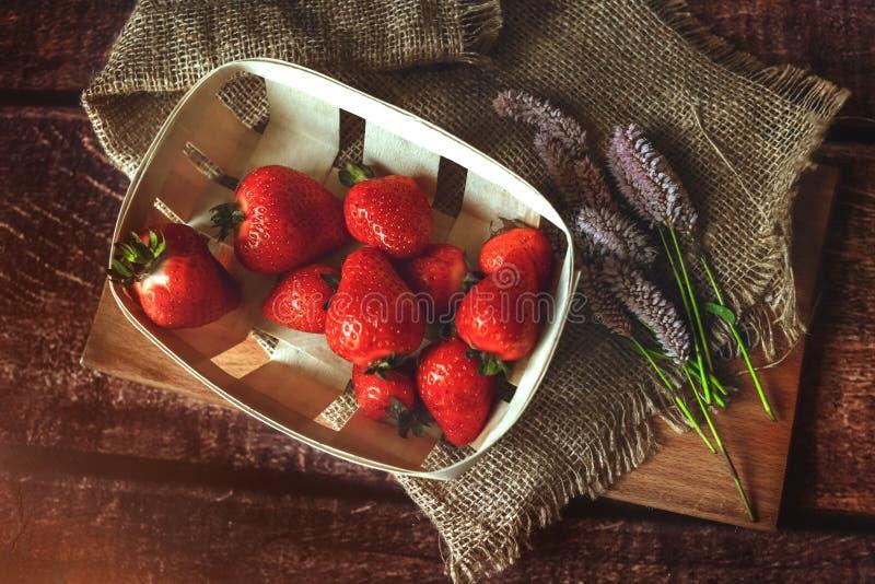 Morangos vermelhas na tabela de madeira com as flores do verão do fiolet, tonificadas fotografia de stock