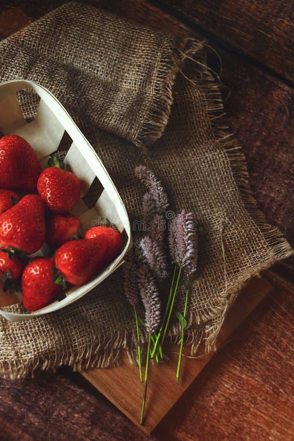 Morangos vermelhas na tabela de madeira com flores do verão, meio tiro, tonificado imagens de stock