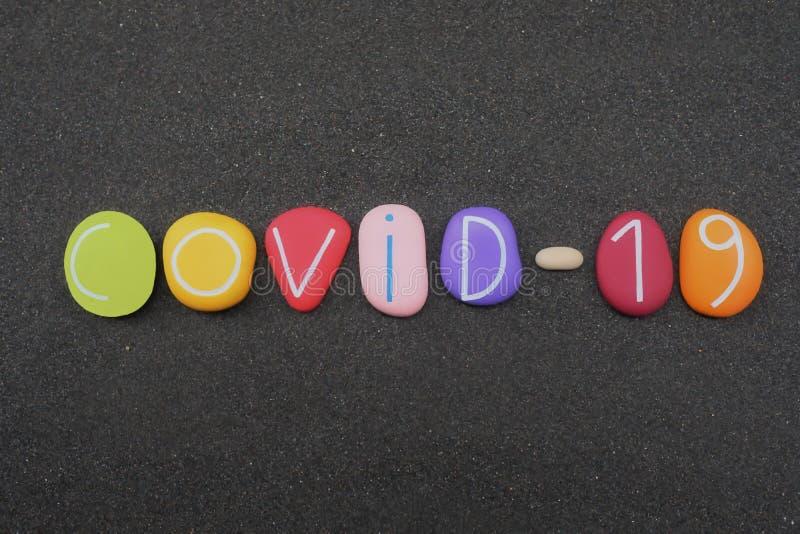 Morbus Coronavirus COVID-19, bestehend aus mehreren farbigen Steinbuchstaben und -ziffern über schwarzen vulkanischen Sand stockfotografie