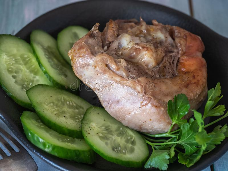 Morceau appétissant de viande frite d'un grand plat d'argile Pommes de terre frites avec la croûte croustillante sur la garniture photo libre de droits