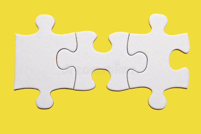 Morceau blanc de puzzle sur le fond jaune photographie stock