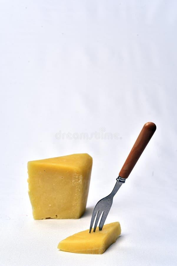 Morceau de cheeseon la table sur le fond blanc images stock