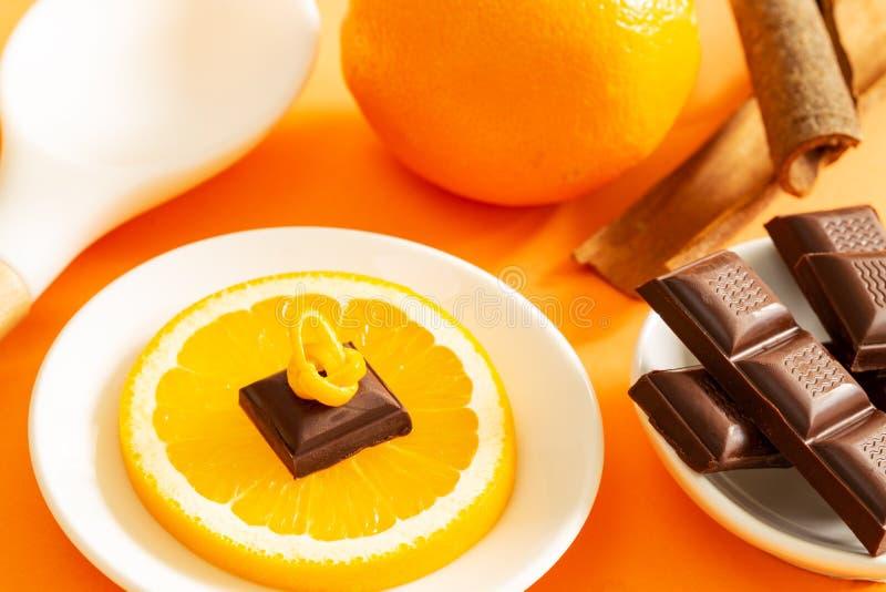 Morceau de chocolat au-dessus de tranche orange, de barres de chocolat, de pleine orange, de bâtons de cannelle et de cuillère à  photographie stock