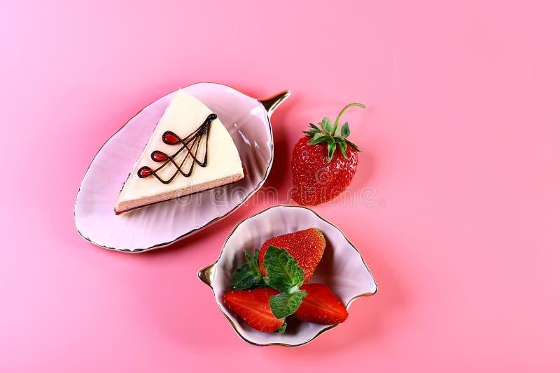 Morceau de deux plats de gâteau au fromage et de fraises fraîches, d'isolement sur le fond rose avec l'espace de copie Vue d'en h photos libres de droits
