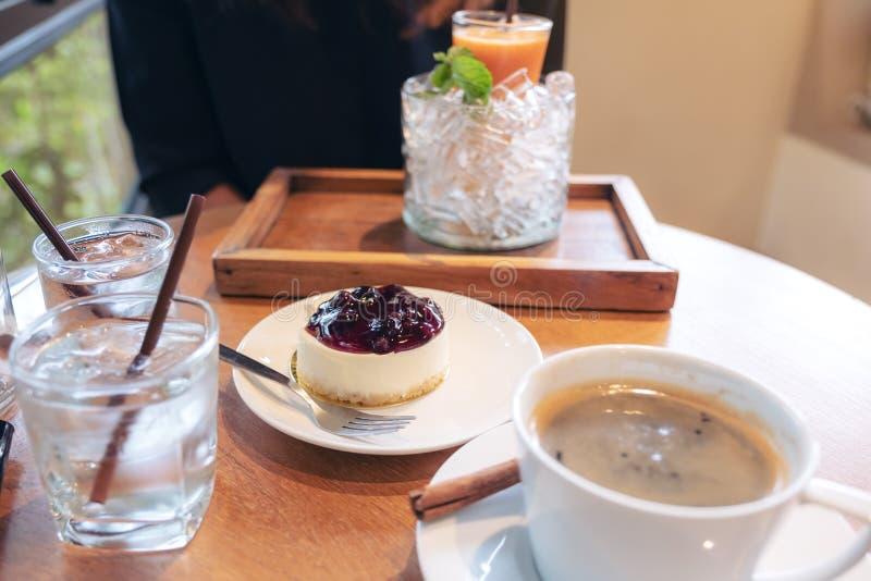 Morceau de gâteau au fromage de myrtille, de tasse de café et de jus d'orange sur la table en bois photos libres de droits