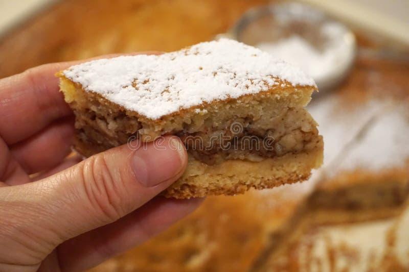 Morceau de gâteau aux pommes libre de gluten chez la main de la femme images stock