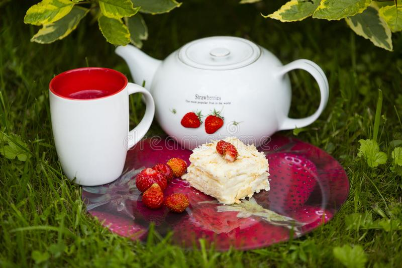 Morceau de gâteau avec la fraise là-dessus, la théière blanche avec la photo de la fraise, la tasse de thé et plusieurs strwberri photographie stock