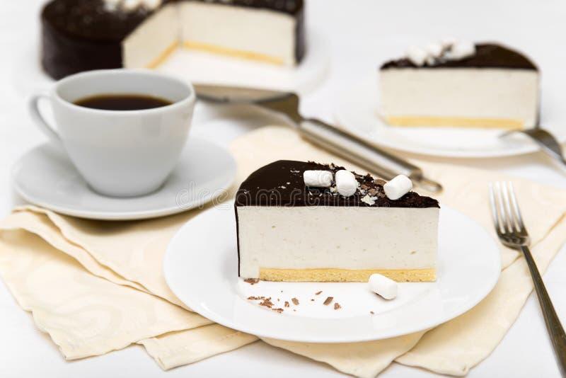 Morceau de gâteau avec le ` de lait du ` s d'oiseau de ` de soufflé, le biscuit, la mousse et le chocolat de noir d'un plat blanc photos stock