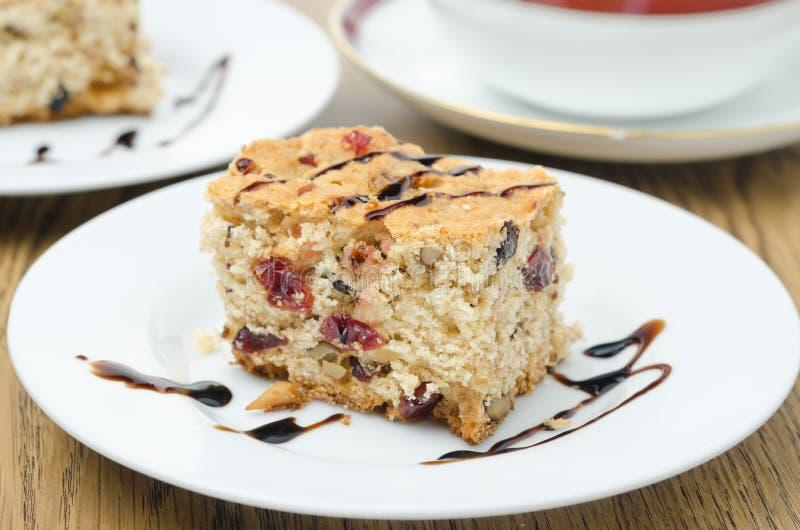 Morceau de gâteau avec les canneberges sèches et les écrous décorés du cho photo stock