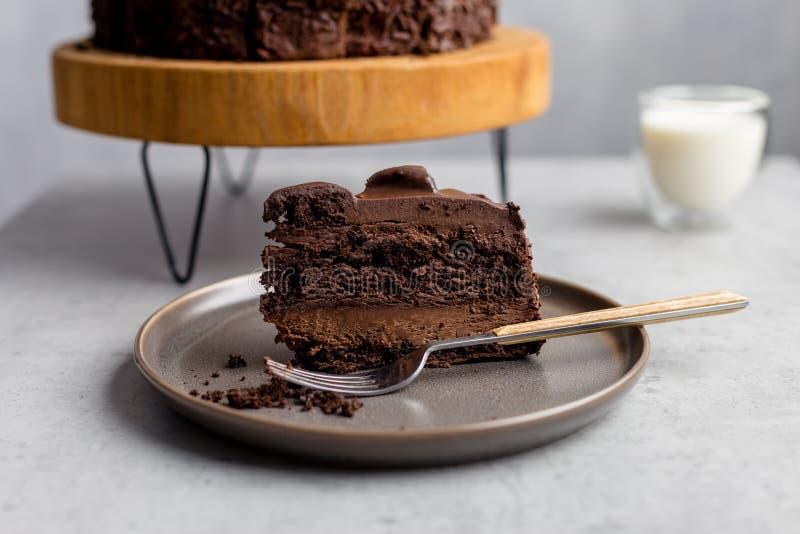Morceau de gâteau de chocolat de plat avec la fourchette sur le fond gris images stock