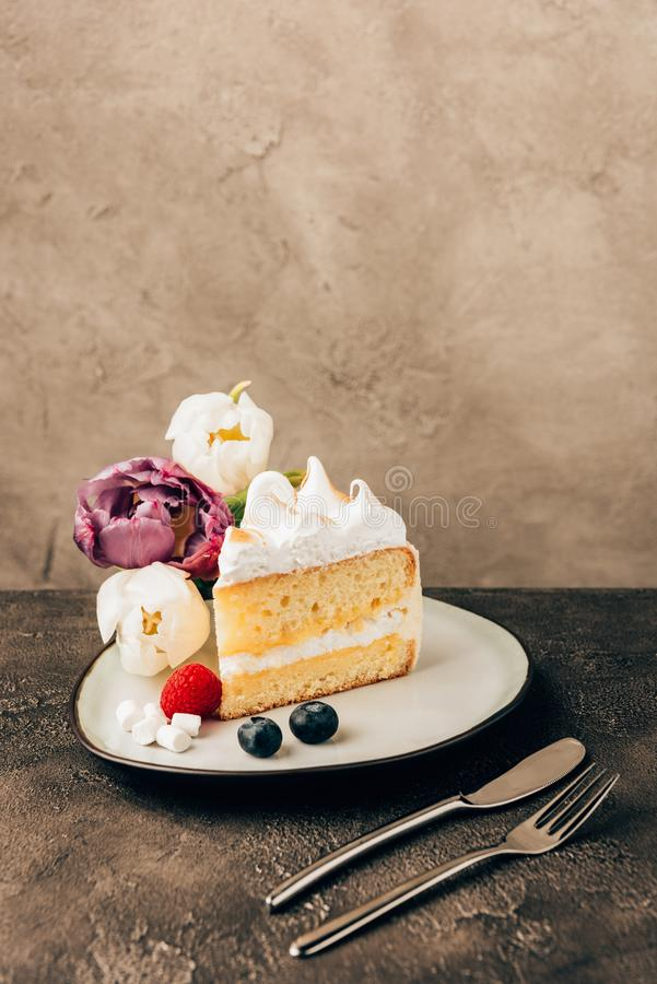 morceau de gâteau délicieux avec la crème fouettée, les baies fraîches et les tulipes photo libre de droits