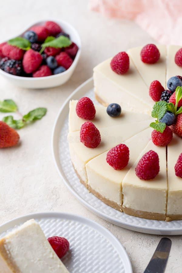 Morceau de gâteau d'anniversaire avec le gâteau entier sur la table blanche image libre de droits