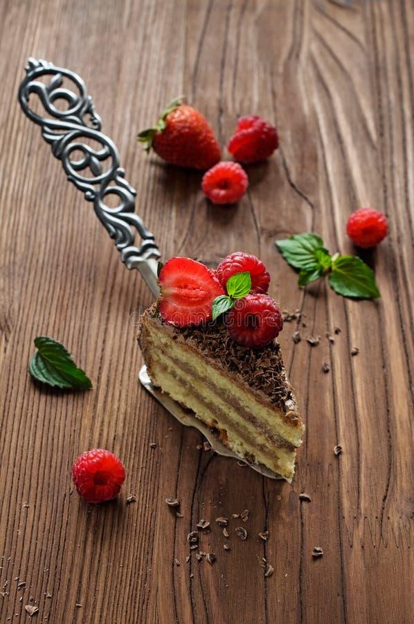 Morceau de gâteau de chocolat avec les baies fraîches photo libre de droits