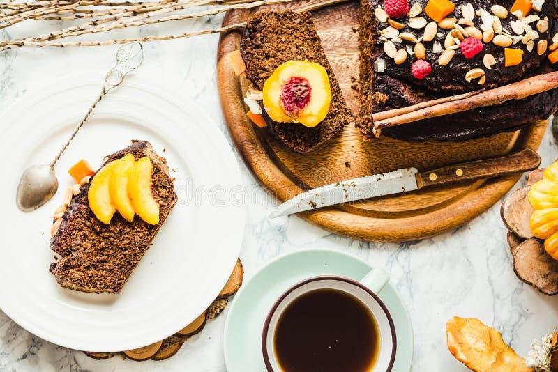 Morceau de gâteau de chocolat avec les pêches de potiron, nuts et fraîches, à photographie stock
