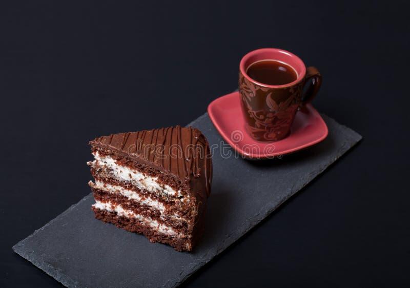 Morceau de gâteau de chocolat et de tasse de café de plat d'ardoise sur le blac image stock