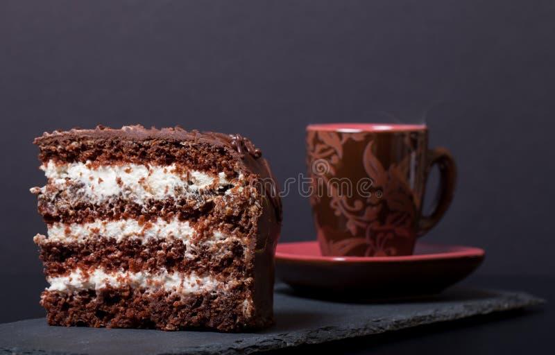 Morceau de gâteau de chocolat et de tasse de café de plat d'ardoise sur le blac photographie stock
