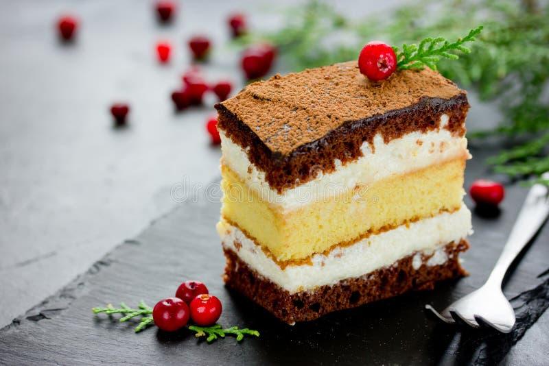 Morceau de gâteau de citron de chocolat de couche décoré des canneberges f photo stock