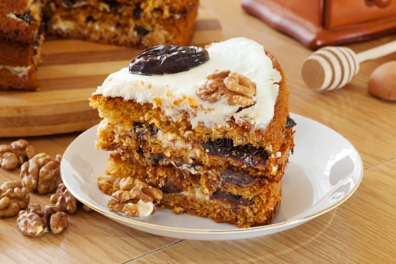 Morceau de gâteau de miel avec la prune et la noix image libre de droits