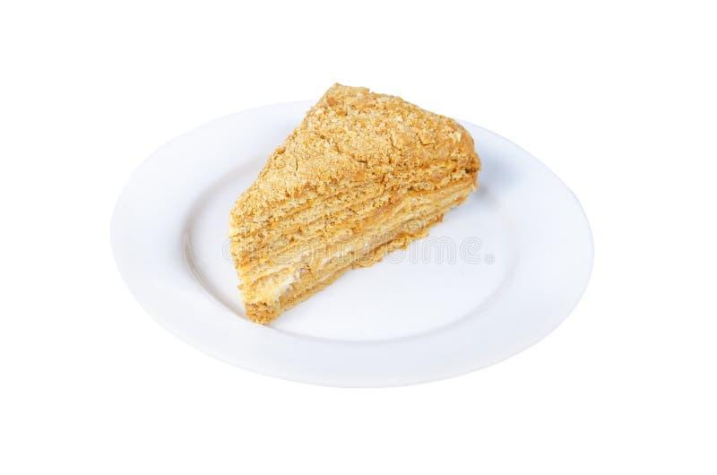 Morceau de gâteau de miel d'un plat blanc d'isolement sur le fond blanc photographie stock libre de droits