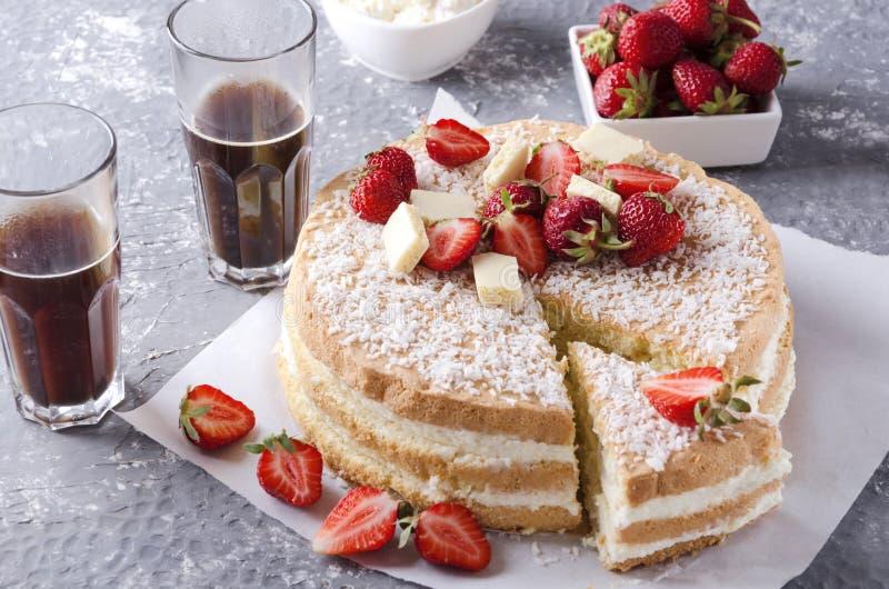 Morceau de gâteau mousseline, fraises, verres de café chaud sur la surface grise Mettant la table pour manger peu de casse-croûte image stock
