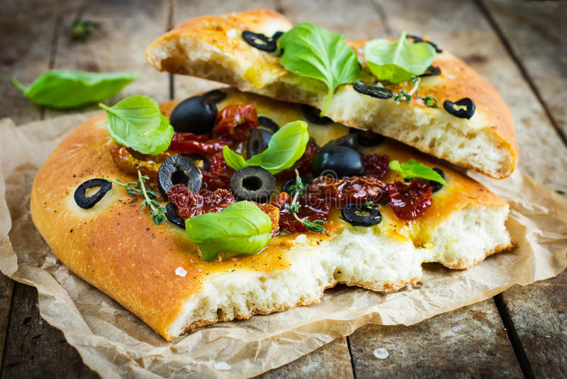 Morceau de pain italien de focacce avec les olives noires, tomatoe sec images libres de droits