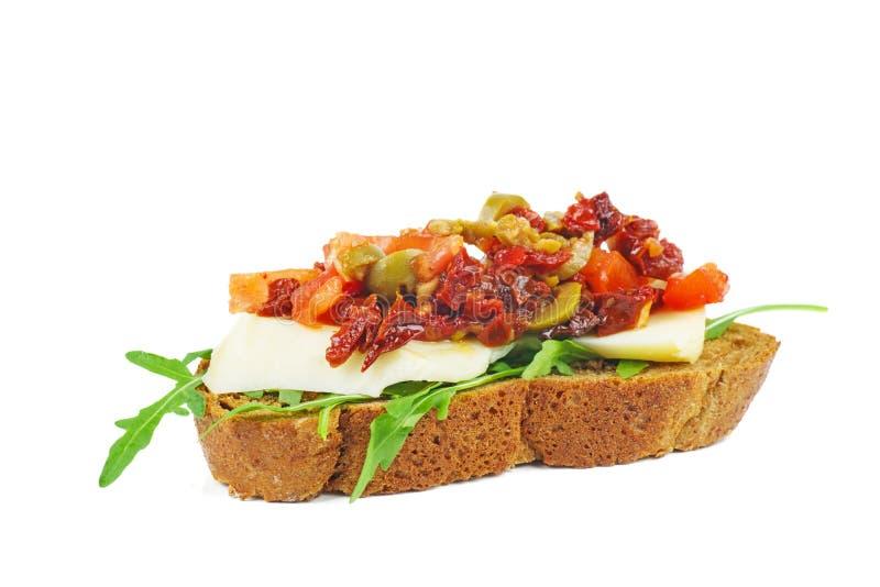 Morceau de pain de seigle avec du fromage, les tomates sèches, les olives et les légumes d'isolement sur le fond blanc images libres de droits