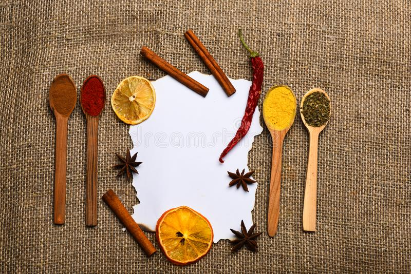 Morceau de papier sur le fond de toile à sac Concept culinaire de recette Cannelle, orange sèche et poivre, anis d'étoile autour photo libre de droits