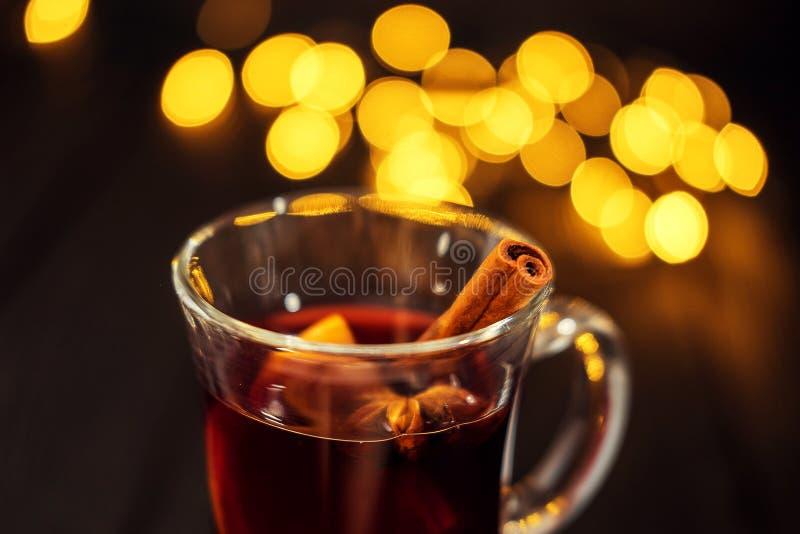 Morceau de plan rapproché de verre de vin chaud avec l'orange et la cannelle sur le fond noir foncé, lumières de Noël, l image libre de droits