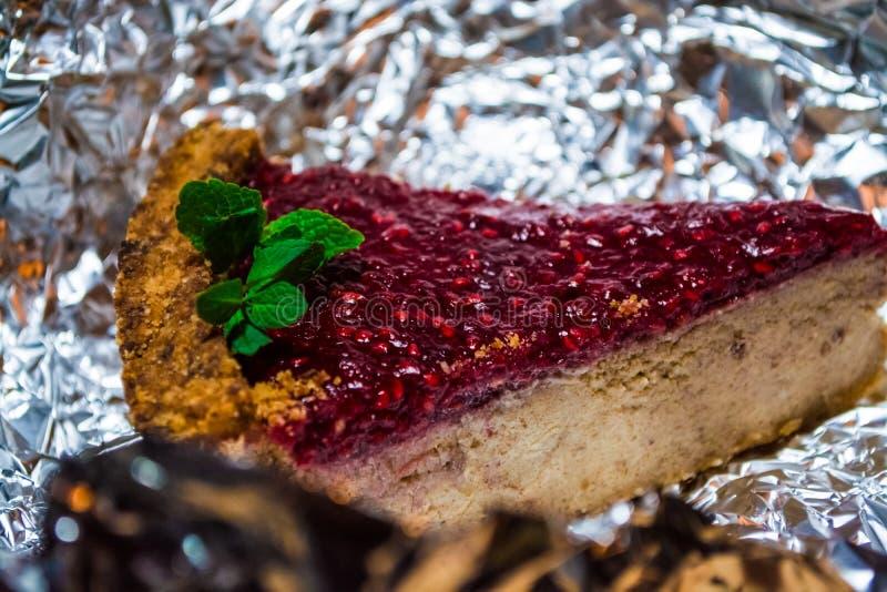 Morceau de tarte frais avec la confiture de la framboise avec une branche en bon état sur le papier de métier Cuvettes de café et photo stock