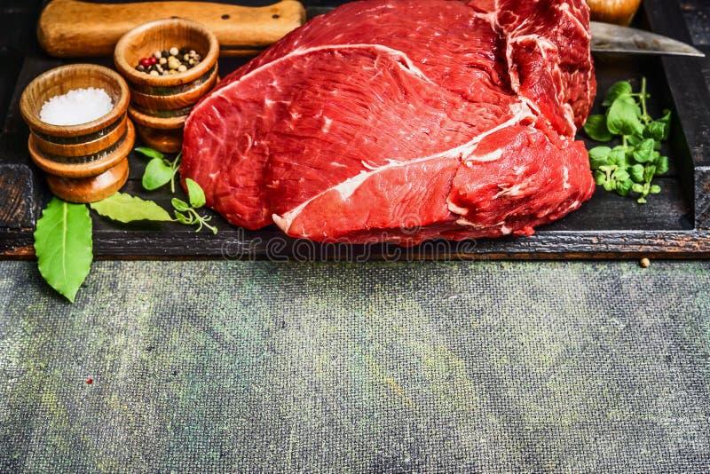 Morceau de viande crue fraîche de boeuf avec faire cuire les ingrédients et le couteau de cuisine sur le fond rustique image stock