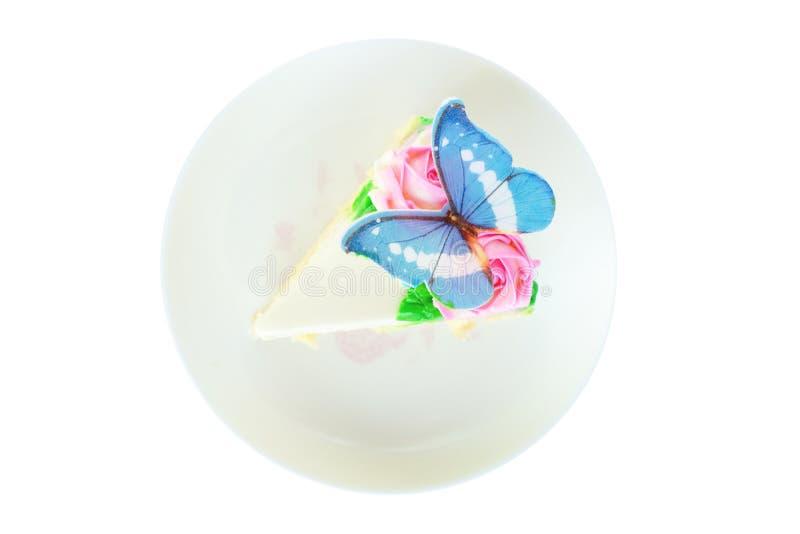 Morceau de vue supérieure de gâteau de vanille décoré de la crème de beurre, de la rose rose et du papillon bleu sur le plat d'is images libres de droits