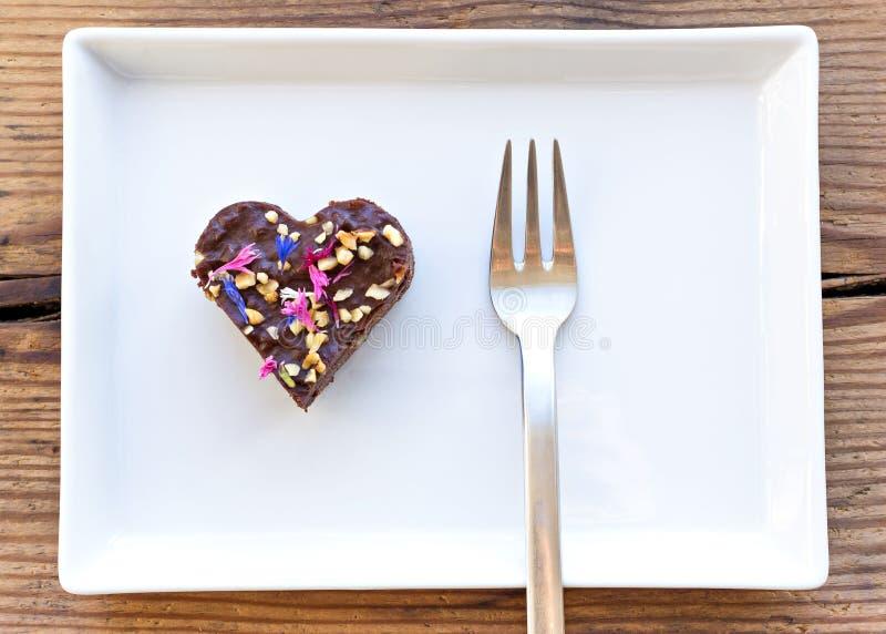Morceau en forme de coeur mignon de gâteau de chocolat arrosé avec des fleurs photos stock