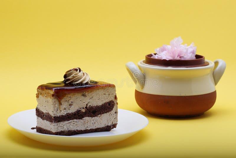 Morceau habillé par caramel de gâteau de crème de chocolat sur le fond jaune photos stock