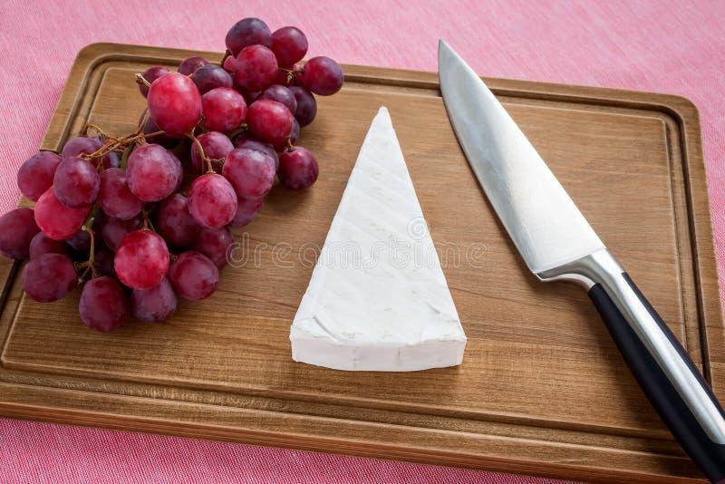 Morceau triangulaire de fromage de brie, de raisins doux rouges et de couteau de chef sur la planche à découper en bois brune Fro image stock