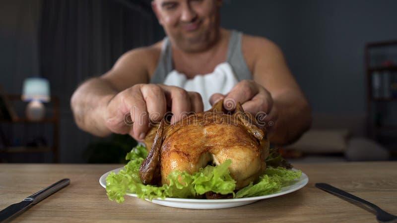 Morceau violent d'homme de poids excessif mal élevé de poulet avec des mains, mangeant avec excès photo libre de droits