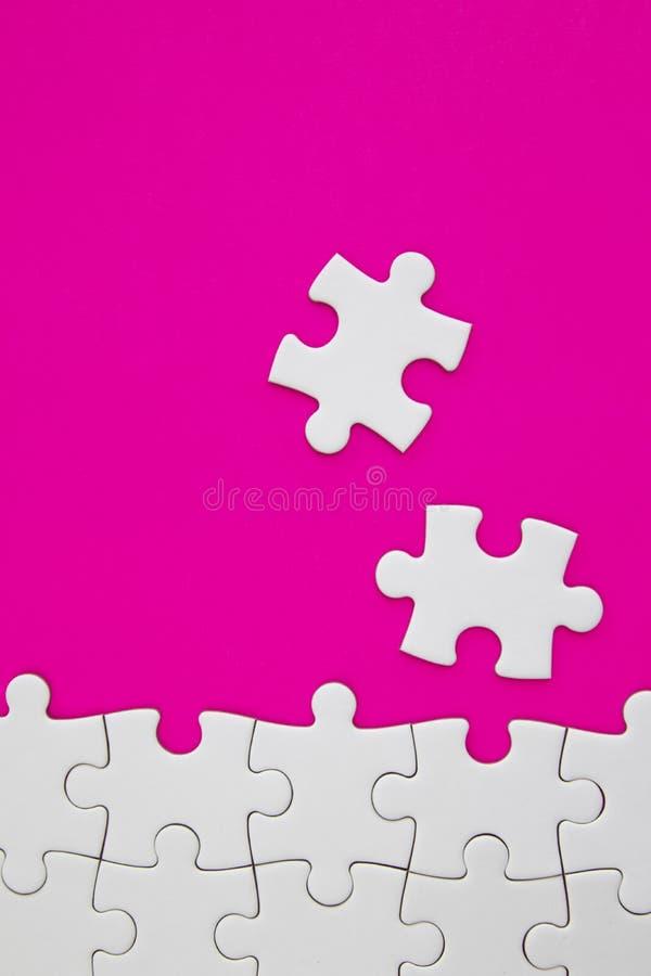 Morceaux blancs de puzzle denteux sur le fond rose avec l'espace négatif photographie stock libre de droits