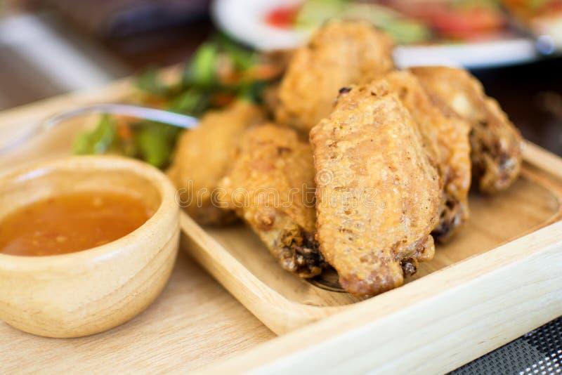 Morceaux croustillants frits de poulet avec de la sauce dans le plat en bois sur la table image libre de droits