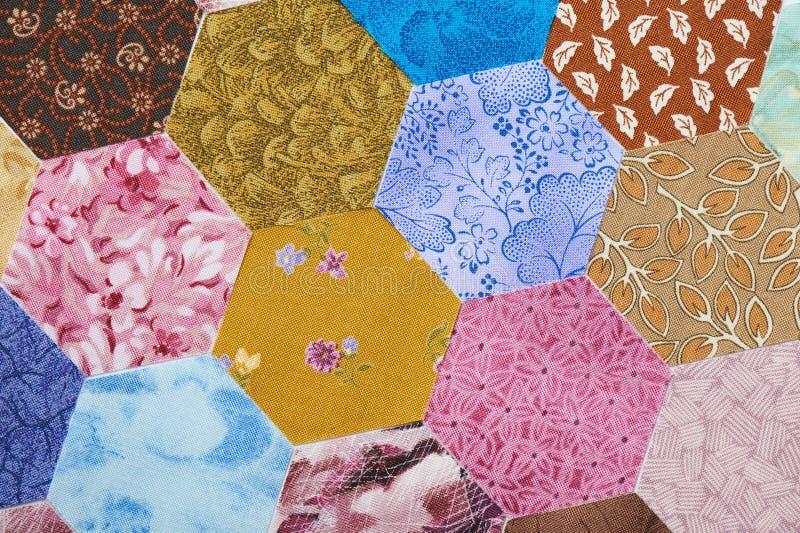 Morceaux d'hexagone d'aléatoire coloré de tissu commandé images libres de droits