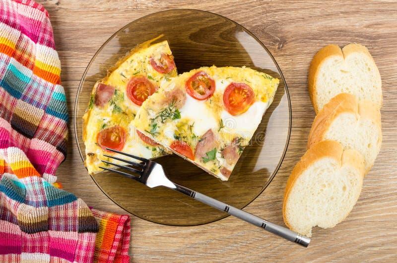 Morceaux d'oeufs au plat avec la saucisse, tomates dans le plat, pain photographie stock libre de droits