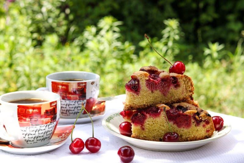 Morceaux d'un tarte avec une cerise et deux tasses de caf? sur une table dehors photographie stock libre de droits