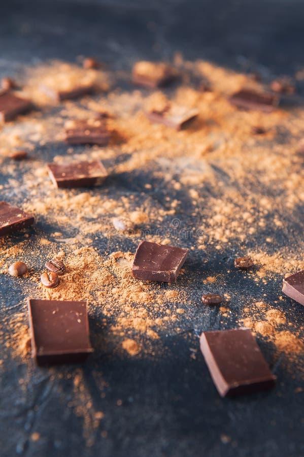 Morceaux de barre de chocolat, poudre de cacao et grains de café sur le fond en pierre foncé Fond avec du chocolat Parts de choco photos stock