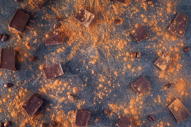 Morceaux de barre de chocolat, poudre de cacao et grains de café sur le fond en pierre foncé Fond avec du chocolat Parts de choco photo libre de droits