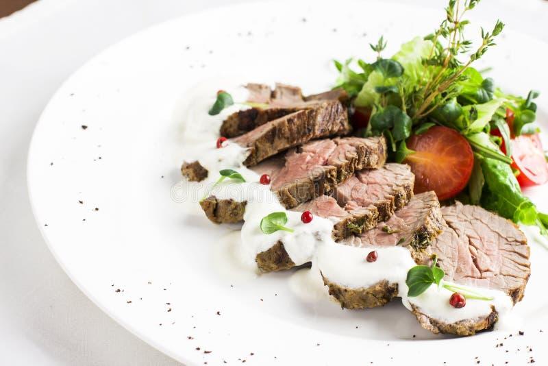 Morceaux de biftecks de boeuf de viande avec de la sauce et des légumes dans le plat blanc image stock