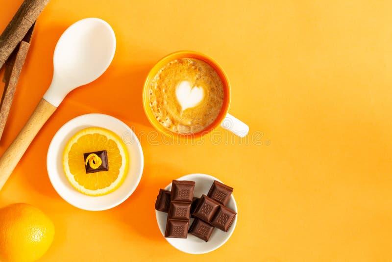 Morceaux de chocolat au-dessus de tranche orange, de barres de chocolat, d'orange, de café de latte, de bâtons de cannelle et de  photo libre de droits