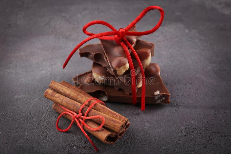 Morceaux de chocolat avec des écrous et des bâtons de cannelle images stock